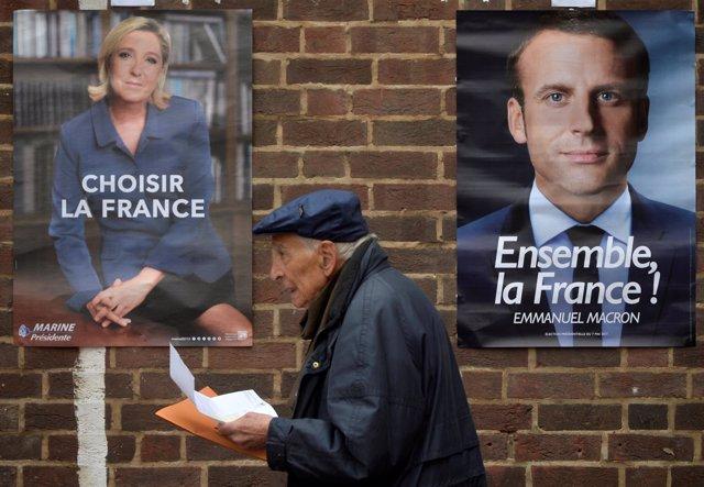 Un hombre pasa entre los carteles electorales de Macron y Le Pen