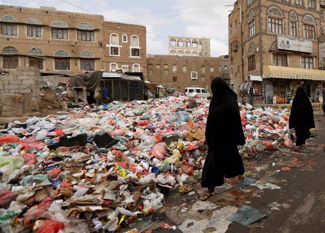 Una mujer pasea junto a basura en Saná