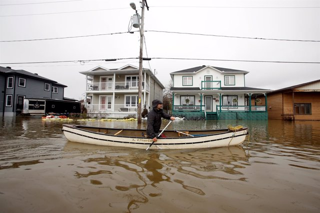 A man paddles a canoe in a flooded residential area in Gatineau, Quebec, Canada,