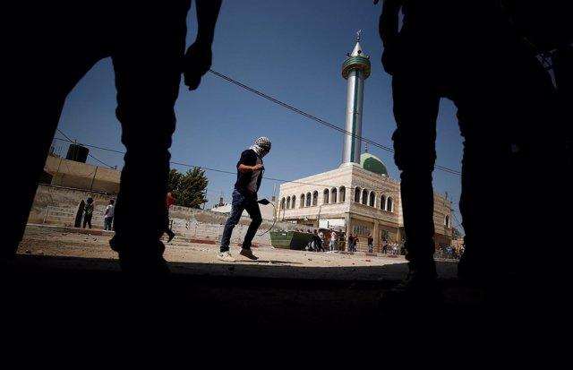 Manifestante junto a militares isralíes en Cisjordania