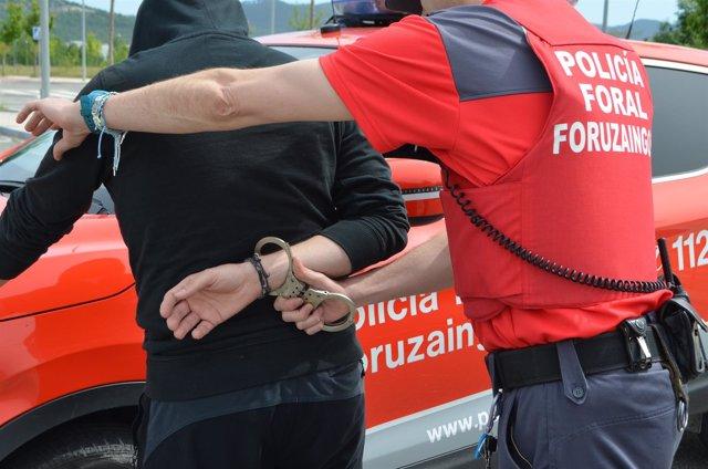 Un policía foral esposa a un detenido