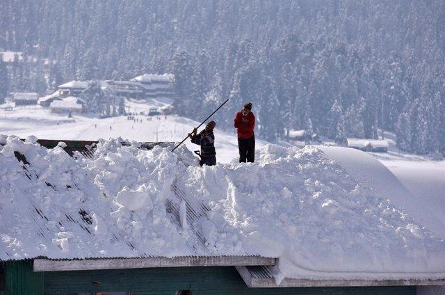 Dos trabajadores retiran nieve en una vivienda en la Cachemira india