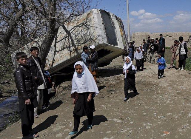 Niñas junto a un autobús dañado por una explosión en Kabul