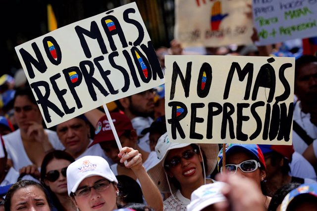 "Demonstrators hold placards that read ""No more repression"" during a women's marc"