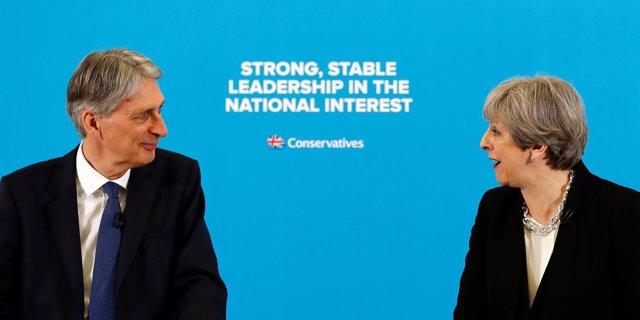 Theresa May junto a su ministro de Finanzas, Philip Hammond