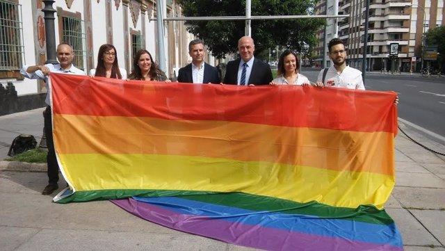 Autoridades posan con la bandera arco iris antes de su izado