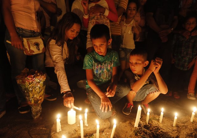 Relatives and residents light candles, in memory of the children who died in a b