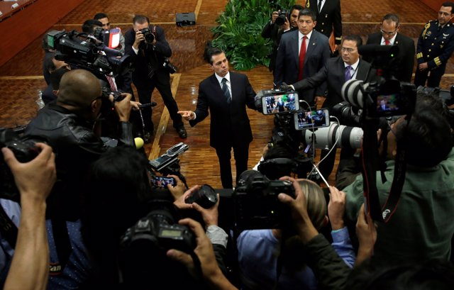 Mexico's President Pena Nieto talks to the media after giving a speech about sla