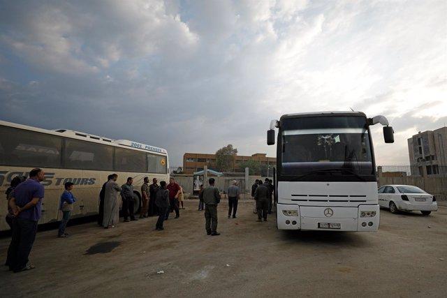 Passengers wait in Qamishli city in Syria's Kurdish-held northeast to embark on