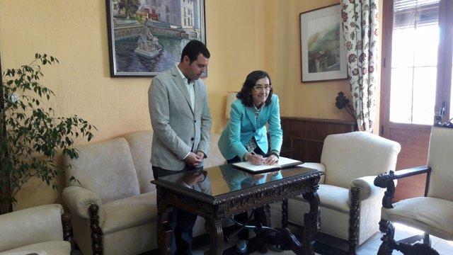 Aguilar firma en el Libro de Honor del Ayuntamiento observada por el alcalde