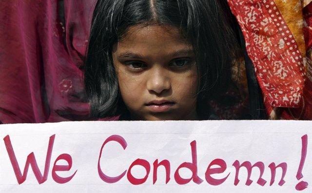Niña con pancarta en una protesta contra la violencia contra la mujer en India