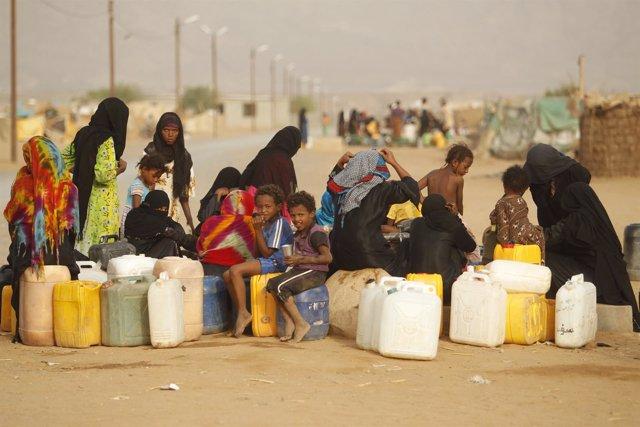 Un grupo de mujeres y niños recolectan agua en un campo de desplazados en Yemen.