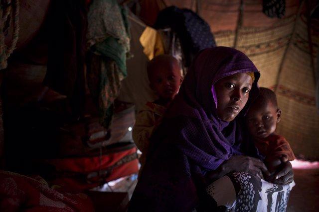 Una madre somalí junto con sus dos hijos enfermos