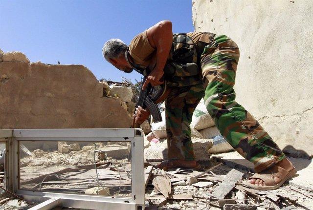 Un soldado del Ejército de Siria Libre se refugia en un enfrentamiento con fuerz