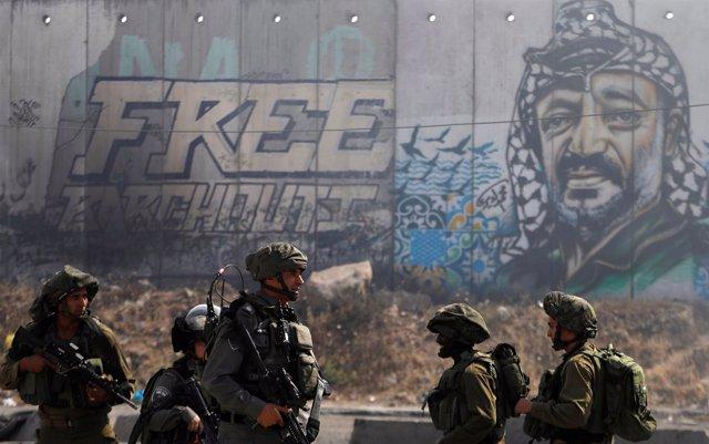 Soldados israelíes frente al muro de Cisjordania