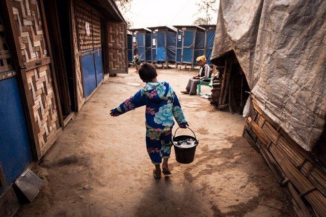 Un niño birmano recogiendo agua para su familia