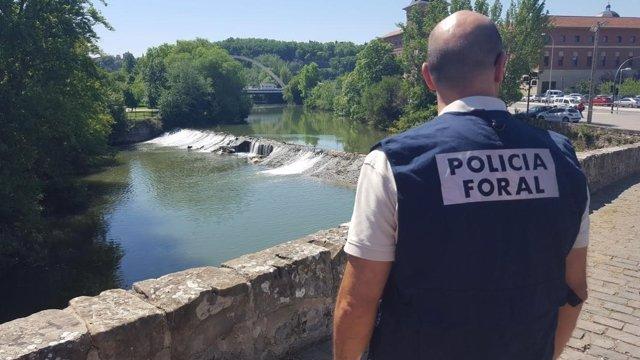 Agente de la Policía Foral junto al río Arga.