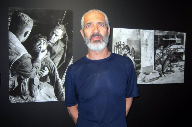 El fotoperiodista Alberto Prieto delante de dos de sus imágenes en Siria