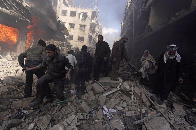 Personas caminan sobre escombros tras un ataque aéreo en Siria