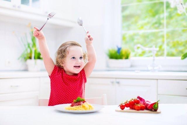 Niña comiendo pequeña, verdura y pasta