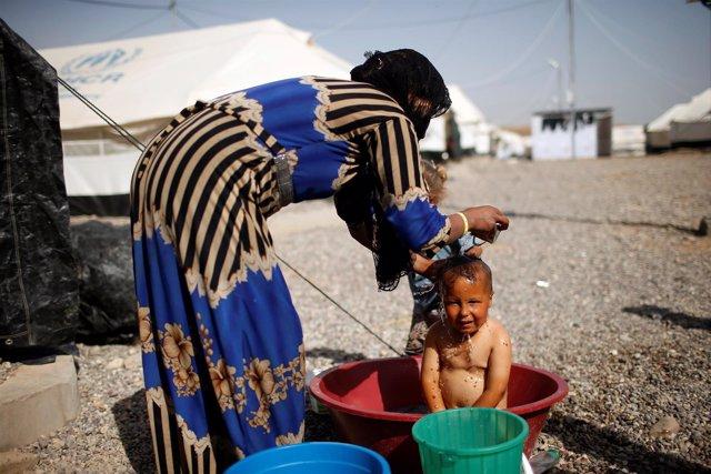 Una madre lava a su hijo en un campo para desplazados de Mosul