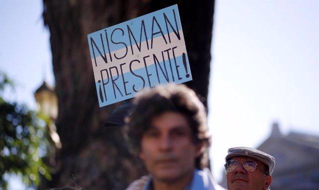 """Un hombre sostiene un cartel que dice """" Nisman presente """""""