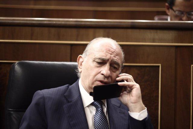 Jorge Fernández Díaz, hablando por teléfono en el hemiciclo