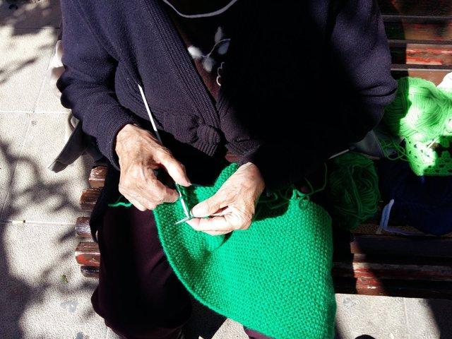 Una mujer teje una manta para visibilizar la Miastenia