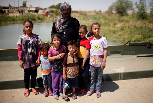 Una mujer iraquí con sus hijos tras huir de Mosul