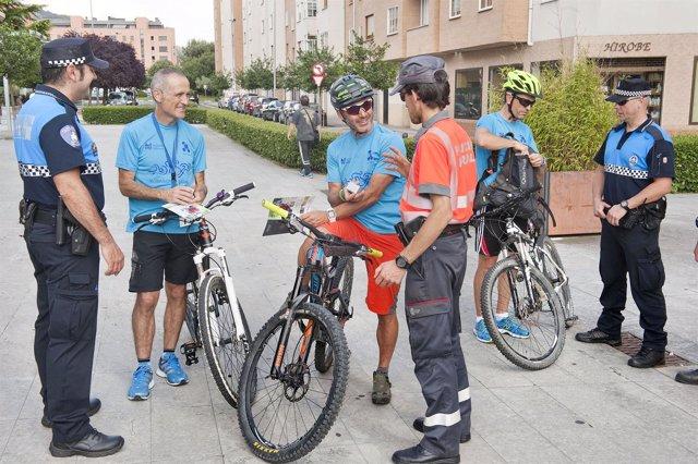 Un policía foral y dos policías municipales informan a un grupo de ciclistas