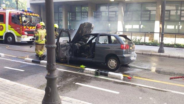 Bomberos tratan de extinguir el incendio de un coche en València
