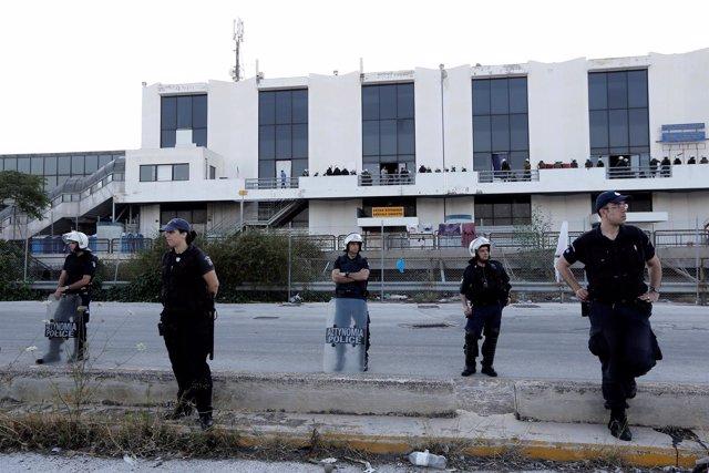 Policías evacúan un campamento de refugiados en el aeropueto de Elliniko