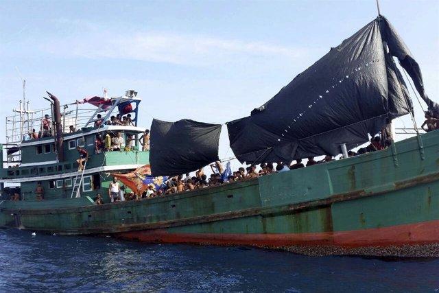 Inmigrantes a bordo de un barco abandonado en aguas del sureste asiático.