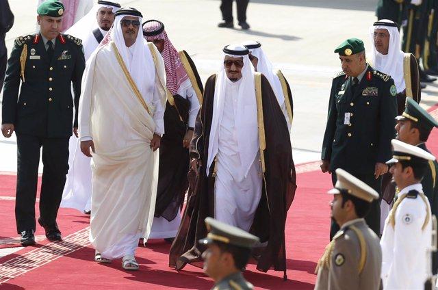 El rey saudí Salman bin Abdulaziz camina con el emir de Qatar Tamim bin Hamad.