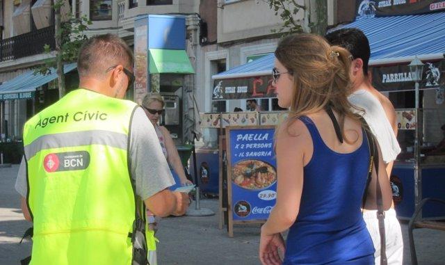 Agente cívico con dos turistas en bañador en la Barceloneta
