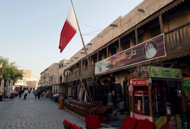 Una tienda con la foto del emir de Qatar y una bandera en Doha