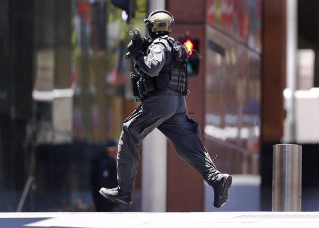 Policía corre hacia la cafetería de Sydney donde se encuentra rehenes.
