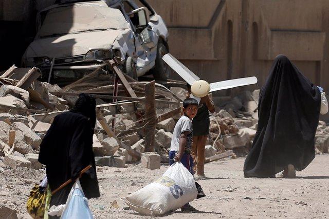 Civiles huyen con sus pertenencias del oeste de Mosul