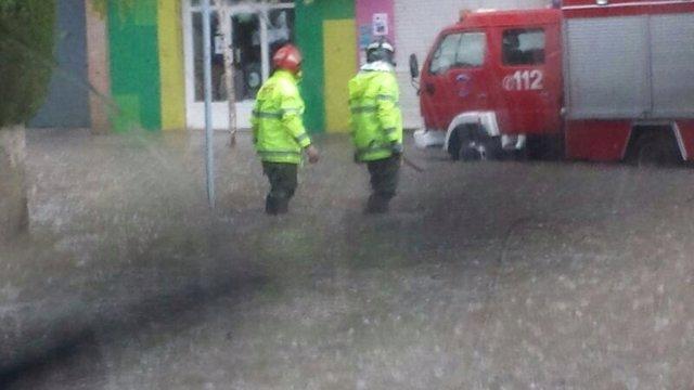 Bomberos en la calle, lluvias y tormenta