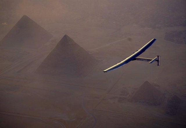 El avión Solar Impulse II sobrevuela las pirámides de Gizeh junto a El Cairo