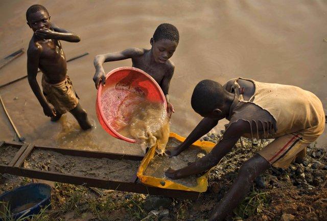 Niños buscan oro en un río en el este de RDC