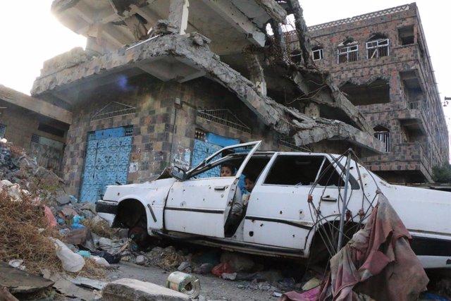 Dos niños juegan en un coche destruido en Taiz