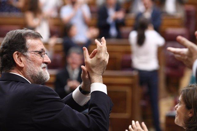 Rajoy aplaude con Pablo Iglesias de fondo tras la votación de la moción