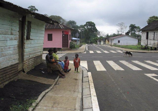 Una familia sentada junto a una carretera en Musola
