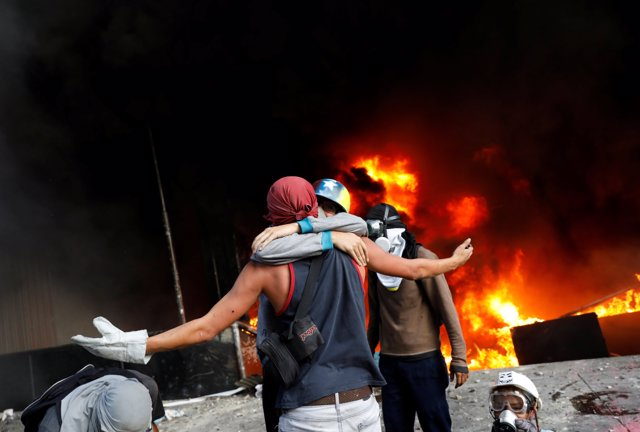 Protesters hug in front of a fire burning at the entrance of a building, housing