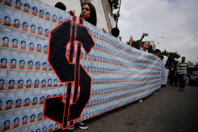 Demonstrators hold a banner made from three thousand two-bolivar-bills, that is