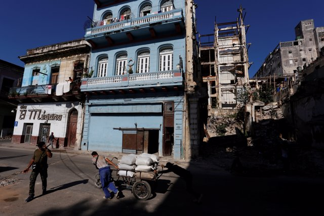 People push a cart past buildings in Havana, Cuba May 16, 2017. Picture taken Ma