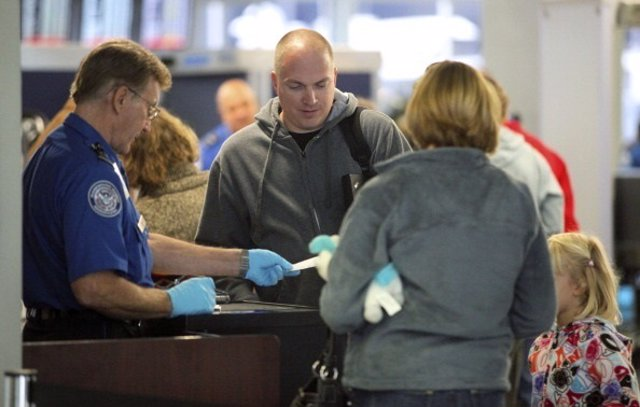 A U.S. Transportation Security Administration agent checks travel tickets at a s