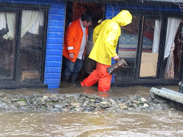 Residents of a house are seen on a flooded street due to torrential rains causin