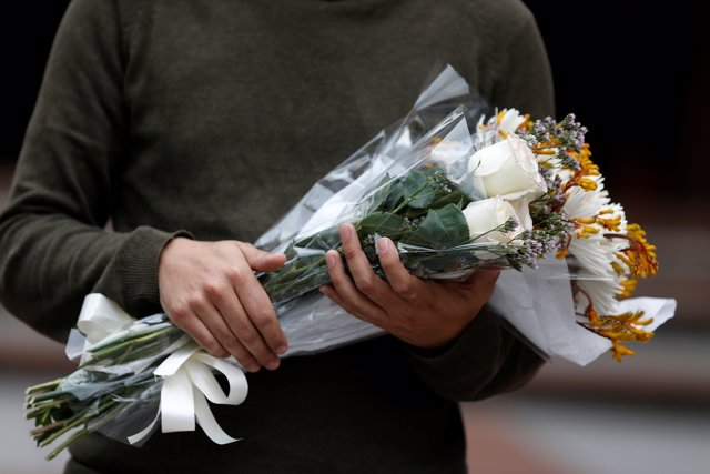A man walks to leave flowers at the Andino shopping center after an explosive de